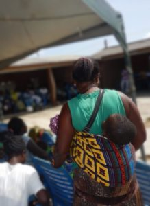 African woman wearing grenn shirt from behind carries child on back in traditional wrap, child's head unsupprted.