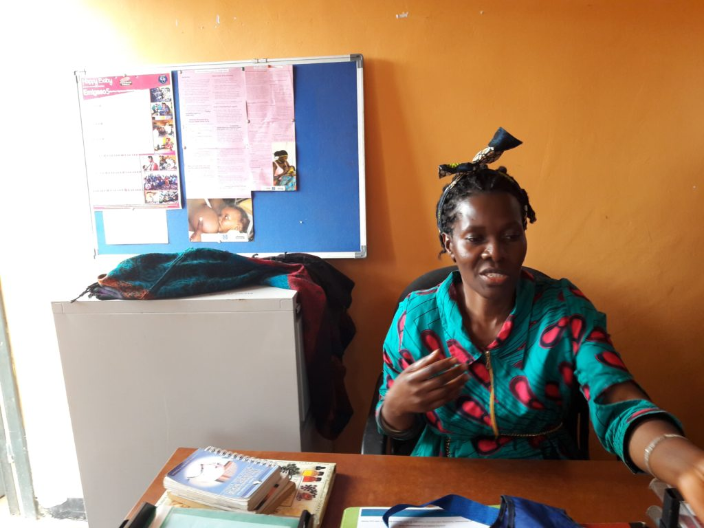 HB project leader Josephine Nalugo sits behind her desk in the CHIABS office