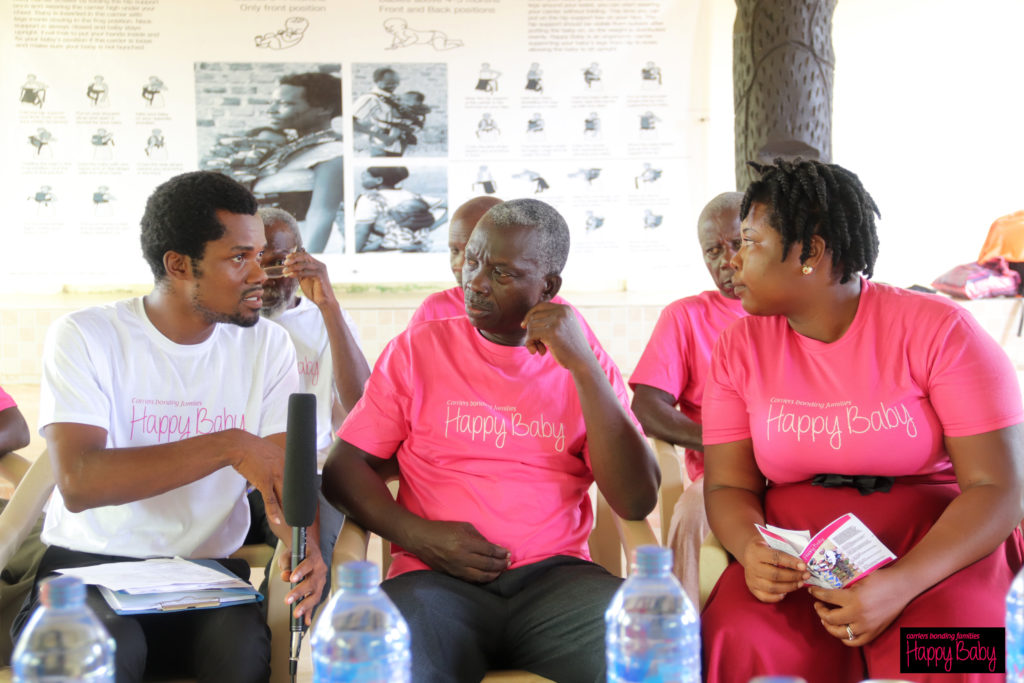 Two men and one woman in pink and white Happy Baby t-shirts sit in chairs during an interview about the benefits of ergonomic baby carriers donated in their community