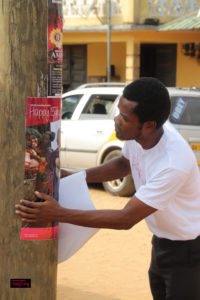 An african man in a white t-shirt staples a Happy Baby educational poster about the benefits of babywearing to a pole.