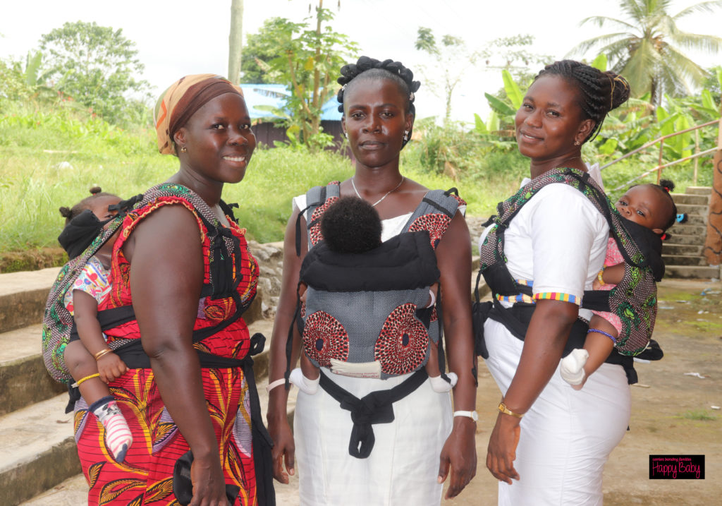 Three African woman wear their infants in Happy Baby ergonomic baby carriers sewn from african kitenge fabric