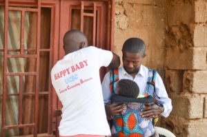 Happy Baby Congo Project Leader Noe Kasali helps a Congolese father wear his baby in a Happy Baby Carrier