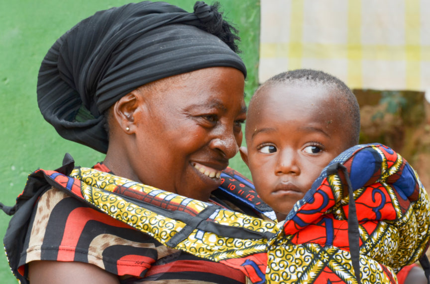 A female African caretaker looks lovingly at a baby in a Happy Baby Carrier, orphaned by the ebola crisis. bonding to help orphans in the Congo